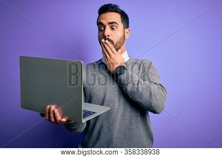 Young handsome businessman with beard working using laptop over purple background cover mouth with hand shocked with shame for mistake, expression of fear, scared in silence, secret concept