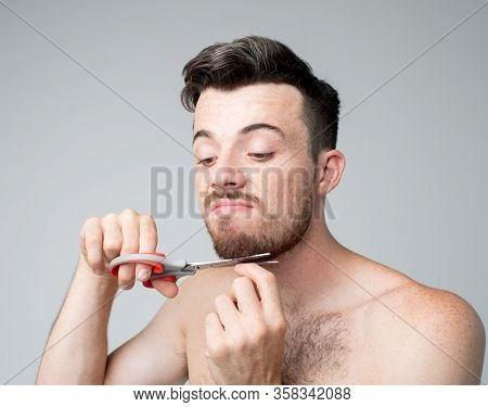 Young Man Isolated Over Background. Portrait Of Guy Trying To Cut His Bearde With Scissors. Self-bar