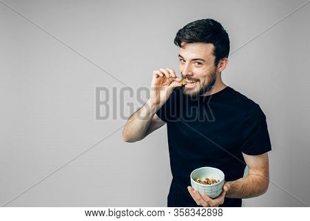Young Man Isolated Over Background. Side View Of Handsome Guy Biting Walnut And Posing On Camera. Ch