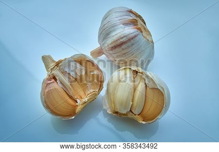 A Lot Of Garlic On A Light Blue Background. Close-up
