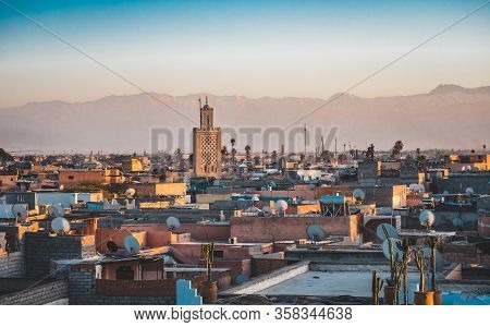 Panoramic Sunset View Of Marrakesh Mdina And The Snow Capped Atlas Mountains In Morocco. View Of Roo