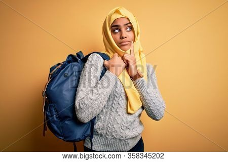 Young african american student girl wearing muslim hijab and backpack over yellow background serious face thinking about question, very confused idea