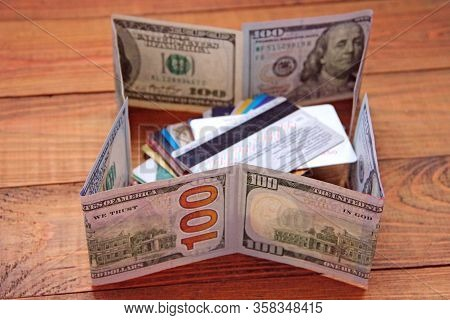 Hundred Dollar Notes And Credit Cards. Stack Of Credit Cards Fenced In Dollars. Cash And Non-cash Mo