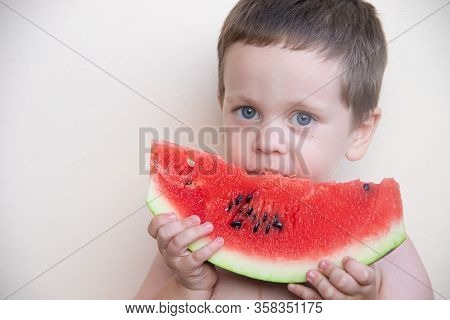 Portrait Of A Boy With A Watermelon . A Happy Child Eats A Watermelon. Summer. A Boy Against A Solid