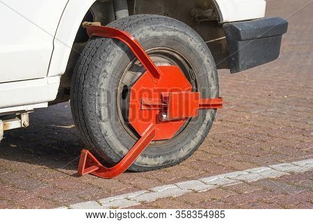 Parking Wheel Lock. Clamped Front Wheel Of Illegally Parked Car, Red Clamp Attached To Wheel. Car Pa