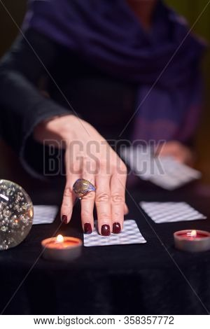 Close-up of woman fortuneteller's hand with fortune-telling cards at table with candles in dark room