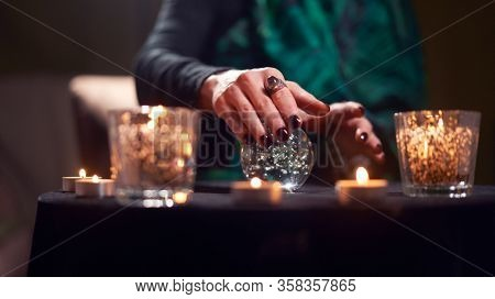 Close-up of fortuneteller female divining on magic ball at table with burning candles