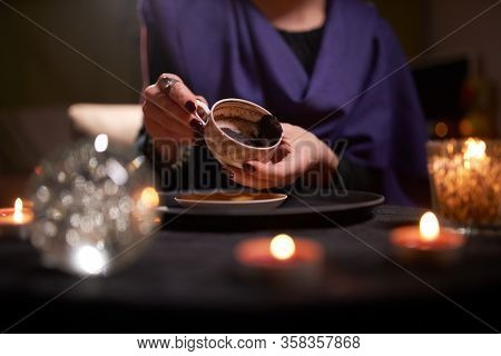 Close-up of woman fortuneteller's hands divining on coffee grounds at table with predictive ball