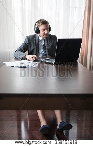 Young Man In Gray Suit, Shirt With Bare Feet In Slippers At Telework Due To Quarantine Of Coronoviru