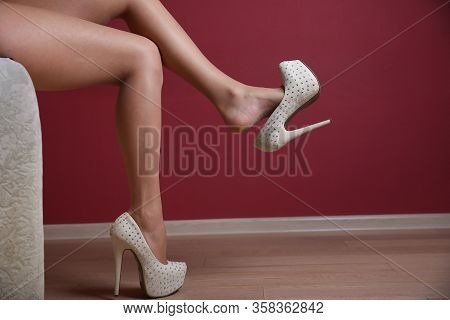 Beautiful Sexy Female Legs In High Heel Shoe Close Up. Foot Fetish Concept. Woman Is Sitting On The