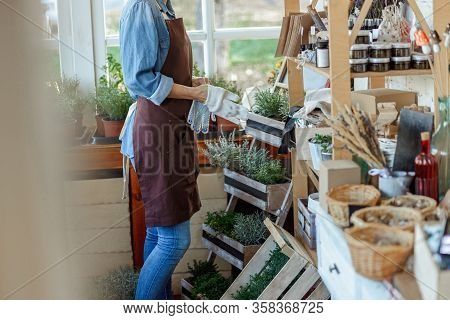 Woman Herbalist Standing Near A Shelf Wooden Rack