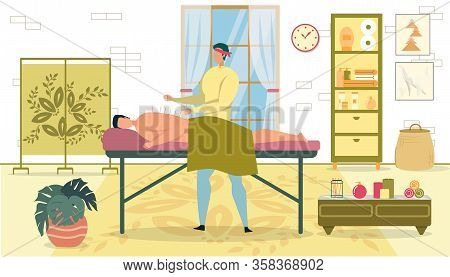 Worker Doing Acupuncture To Man Lying Down Relaxing On Table In Salon. Cabinet With Towel, Shelf Wit