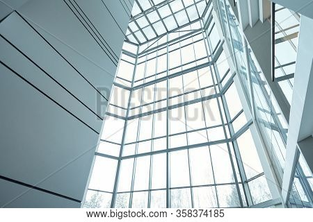 Part of interior of large contemporary multi-floor office building or business center with windows, walls and balconies