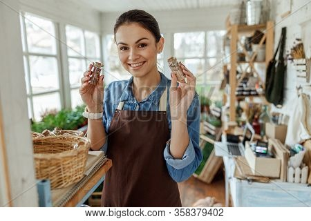 Female Herbalist With Small Bottles Looking Forward