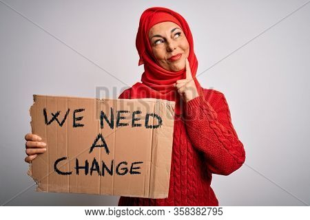 Middle age woman wearing muslim hijab asking for change holding banner serious face thinking about question, very confused idea