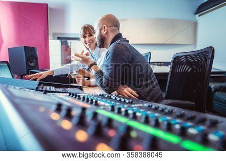 Sound engineer and singer or musician discussing the mix of a production