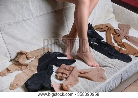 Woman Legs In Tights And Different New Pairs Of Tights On The Sofa