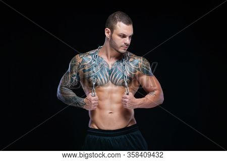 Tattooed Strong Muscular Athletic Man Holding Metal Chain Over His Neck On Black Background