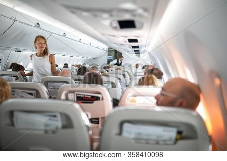 Pretty, young woman aboard an airplane during a lang haul commercial flight - stretching her legs a bit, walking in the aisle