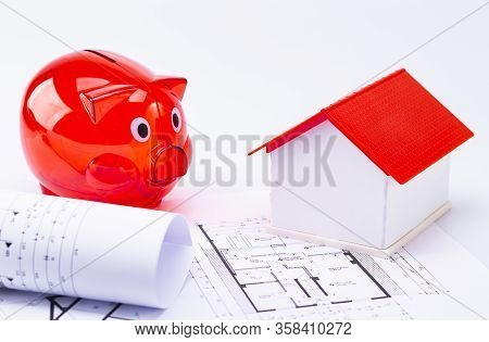 The Photo Shows A Red Piggy Bank With A Model House And Floorplan, Isolated On A White Background