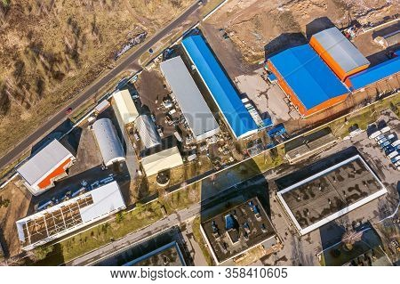 Aerial View Of Suburb Industrial Area With Group Of Modern Warehouses, Factory Buildings And Distrib