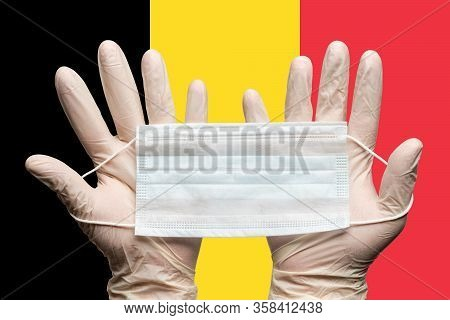 Doctor Holding Medical Face Mask In Two Hands In White Gloves On Background Flag Of Belgium. Concept