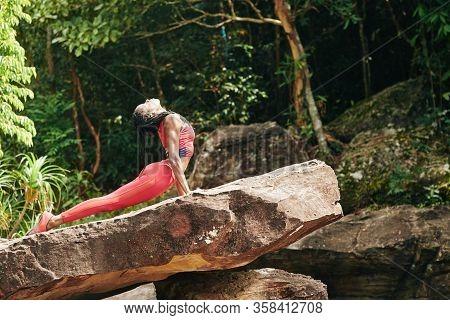 Fit Beautiful Black Young Woman In Bright Orange Top And Leggings Doing Cobra Asana