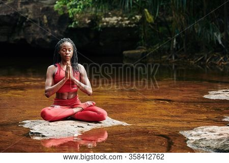 Calm Fit Young Woman Meditating In Lotus Position On Rock In Forest River