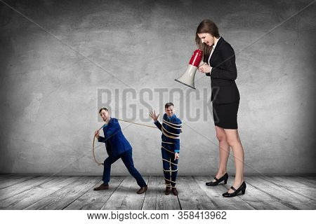 Strict Boss With Megaphone Gives Orders To Subordinate And He Pulls Tied Himself With A Rope. Over G