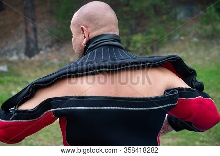 Diver Puts On A Wetsuit. Close Up Of Diver In Wet Suit Prepares For The Dive, Checks And Puts On The