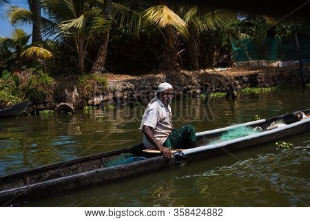 Kerala, India-February 4, 2019. An Indian male fisherman on a traditional wooden boat sails through