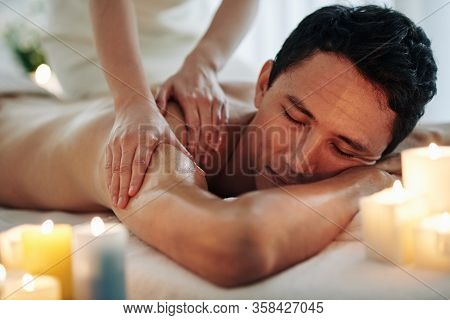 Handsome Middle-aged Man Enjoying Relaxing Spa Massage With Oils