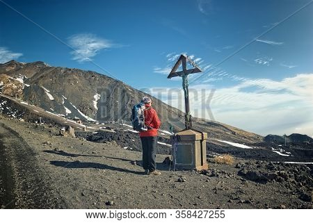 ETNA NATIONAL PARK, SICILY, ITALY - NOVEMBER 25, 2007: hiker praying in front the crucifix on the path to Etna Summit Craters in Sicily