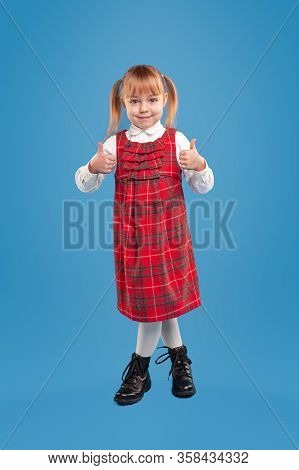Cute Little Girl In Red Checkered Sundress And White Elegant Shirt And Black Shoes Smiling At Camera