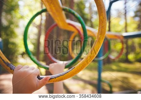 Hands Of A Little Boy Hold On To The Crossbar At The Playground. The Kid Is Climbing The Monkey Bar