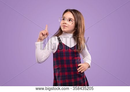 Clever Little Child In School Uniform And Glasses Keeping Hand On Waist And Pointing Up During Studi