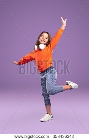 Cheerful Little Girl In Bright Orange Jumper And Jeans With White Headphones On Neck Having Fun Stan