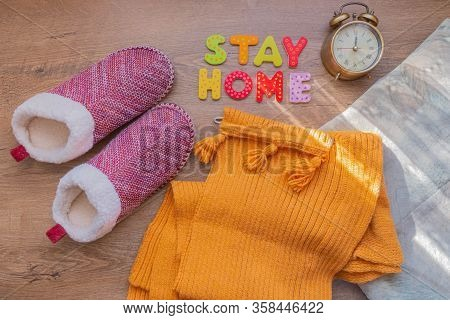 Words Stay Home Of Wooden Letters, Alarm Clock, Pillow, Scarf, And Slippers On Wood Background. Text