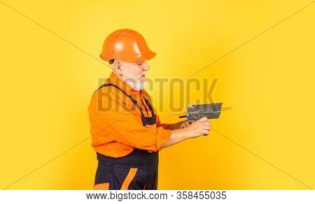 He Needs Little Break. Plasterer In Working Uniform Plastering. Man With Spatula. Process Of Applyin