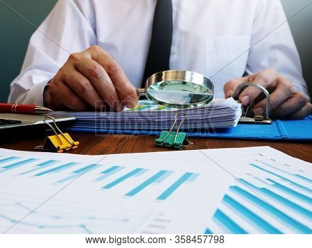 Auditor Makes Internal Audit Of Company And Checks Financial Report With Magnifying Glass.