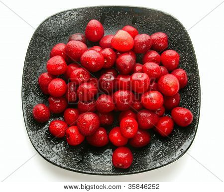 Sweet cherries on black dish