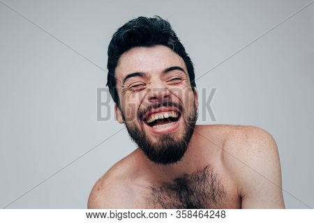 Young Man Isolated Over Background. Laugh Of Madness. Naked Chest. Sit Alone In Room. Mental Disorde