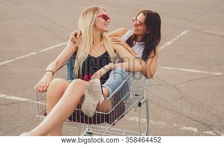 Delighted Young Women Smiling And Looking At Each Other While Sitting In Shopping Cart On Parking Lo