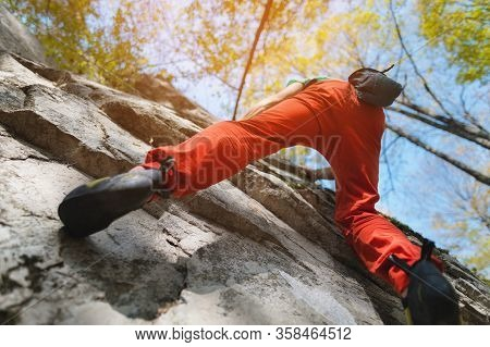 A Free Aged Male Climber Hangs On A Rock Wall In A Forest In The Mountains. Mature Sports Concept