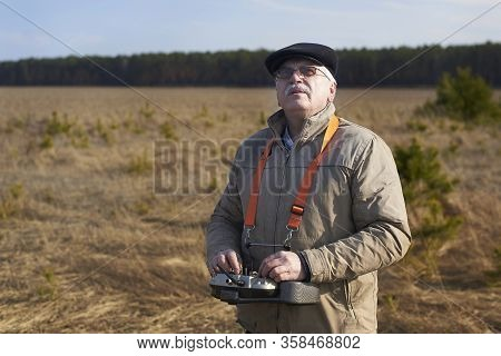 An Elderly Man Controls A Radio-controlled Aircraft Using The Remote Control On The Field In Early S