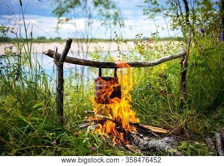 Camping, A Burning Fire, A Kettle Basked On An Open Fire. Summer Camping.