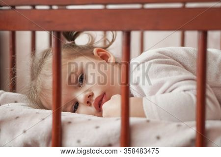 Little Girl Three Years Old In A Pink Pajamas Lies On Her Stomach In A Cradle. Sleepy Baby Lies In T