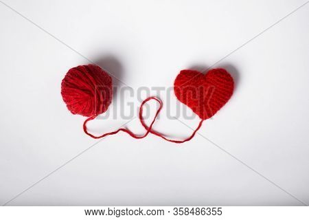 Close Up Of A Wool Ball And Heart Shape On White Background. Heart Shaped Woolen Yarn. Love Crochet.