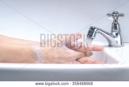 Woman Washing Hand With Soap Foam And Tap Water In Bathroom. Hand Clean Under Faucet On Sink For Per