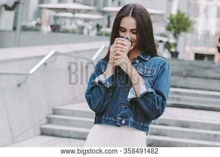 Young Happy Hipster Girl In Stylish Denim Jacket Enjoying Morning Coffee On The Go. Beautiful Cheerf